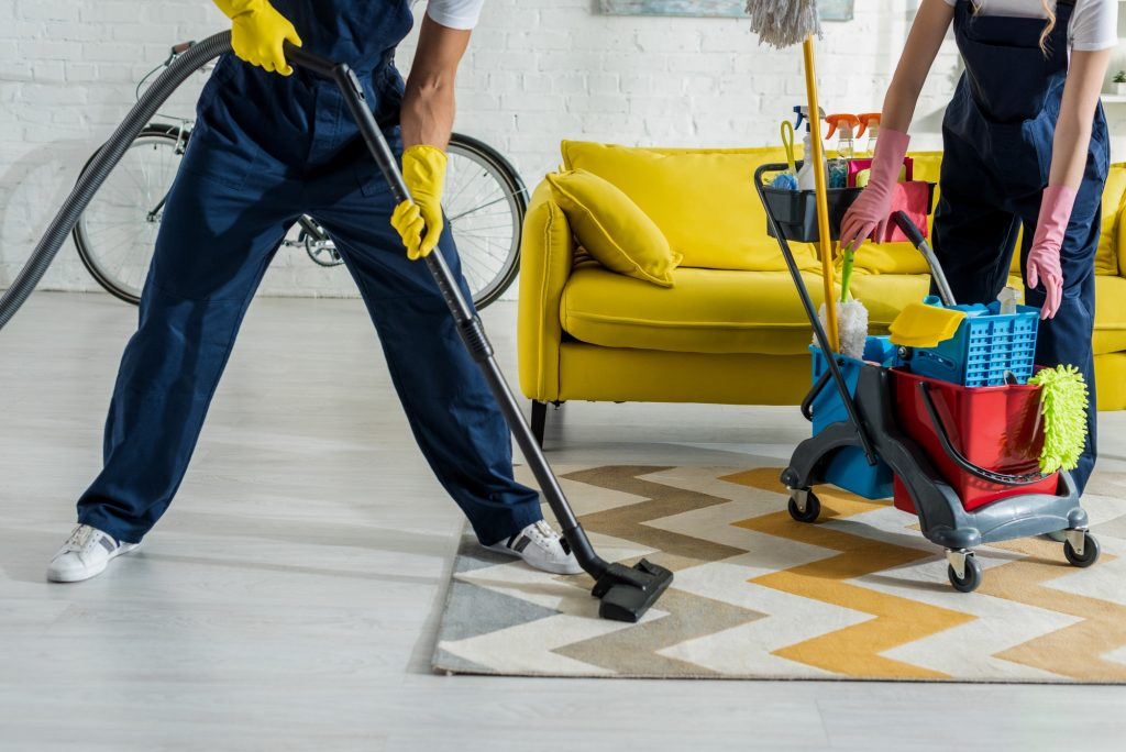 cropped view of cleaners in overalls cleaning apartment